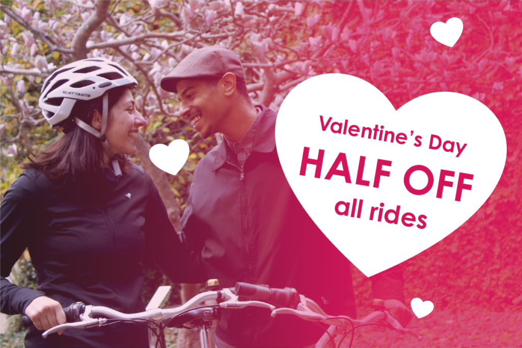 Photograph of a couple biking in Downtown Pittsburgh with a graphic describing half off Healthy Ride PGH rides on Valentine's Day