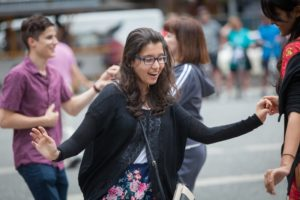 Photo shows young woman dancing in Market Square, Pittsburgh