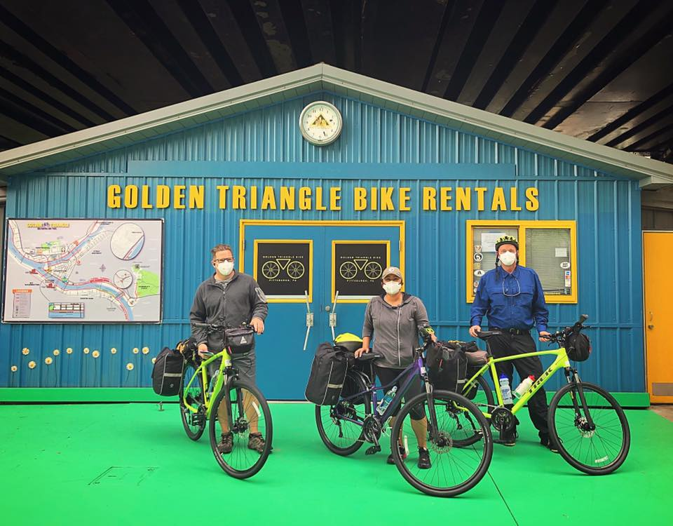 Photo shows three bikers wearing face masks posing in front of Golden Triangle Bike Rentals