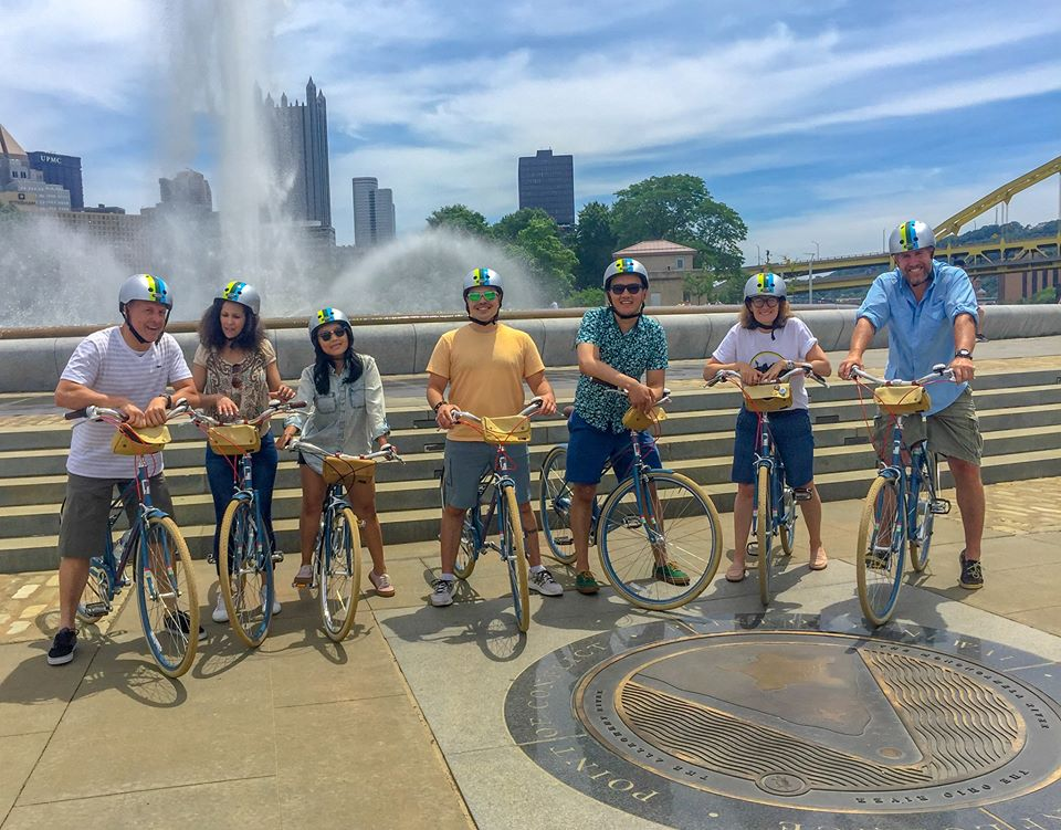Photo shows a group of visitors on bicycles at Point State Park, with the fountain and city skyline in the background