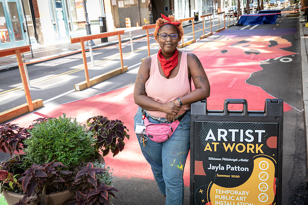 Photo shows artist Jayla Patton standing in front of a red, orange, and purple painted Penn Avenue in Downtown Pittsburgh